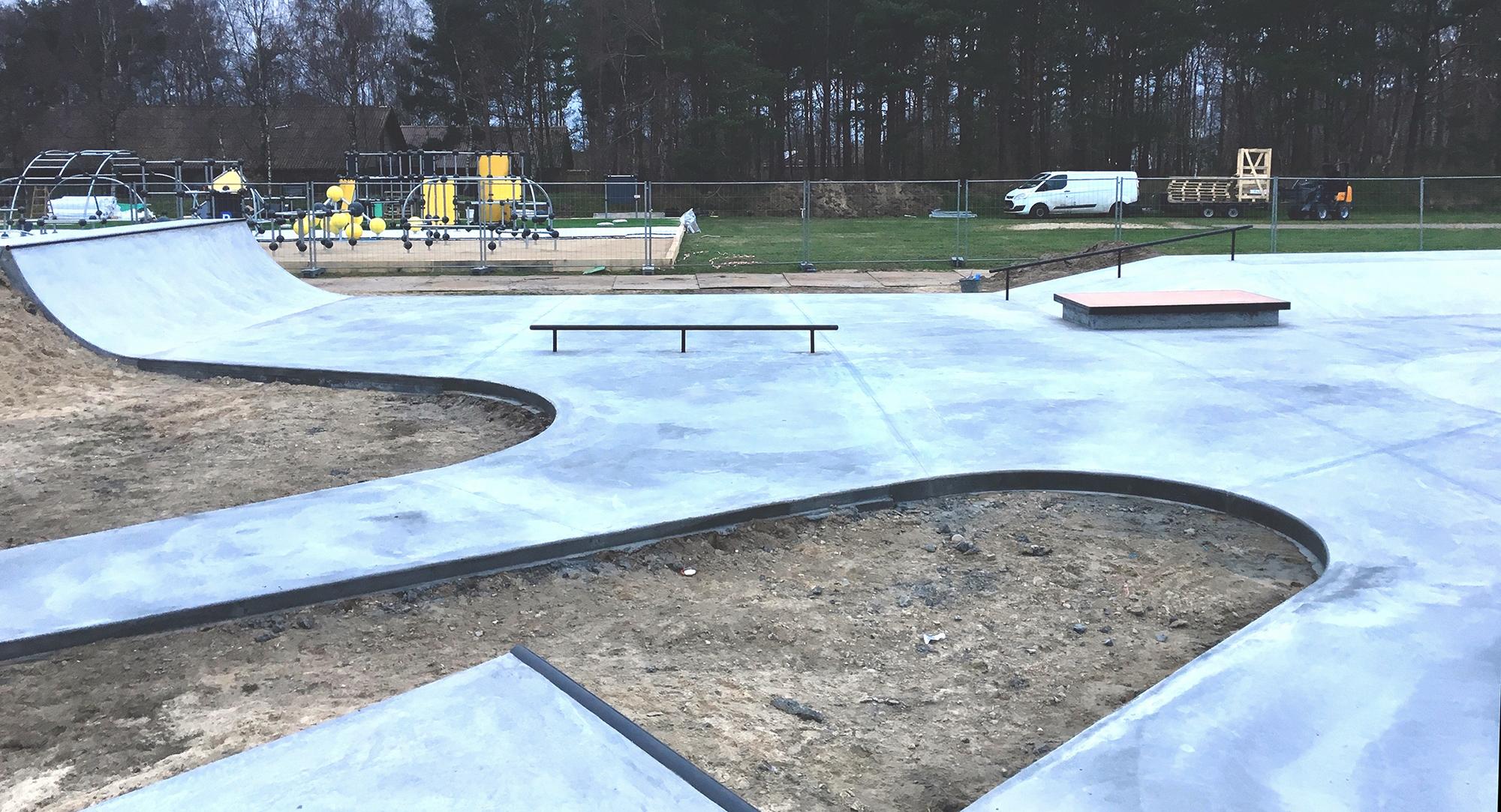 Brede stiet i beton omkranser rå jord på en byggeplads med en næsten færdig skatepark