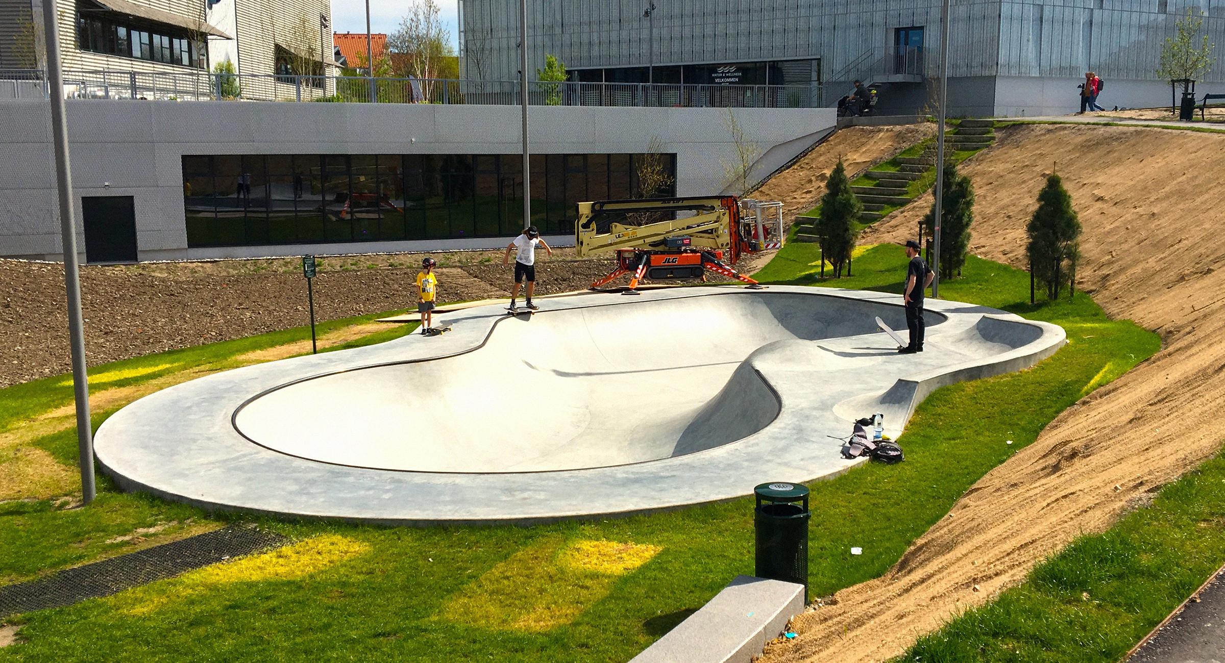 En arkitekttegnet bowl i beton bliver skatet af tre unge mænd