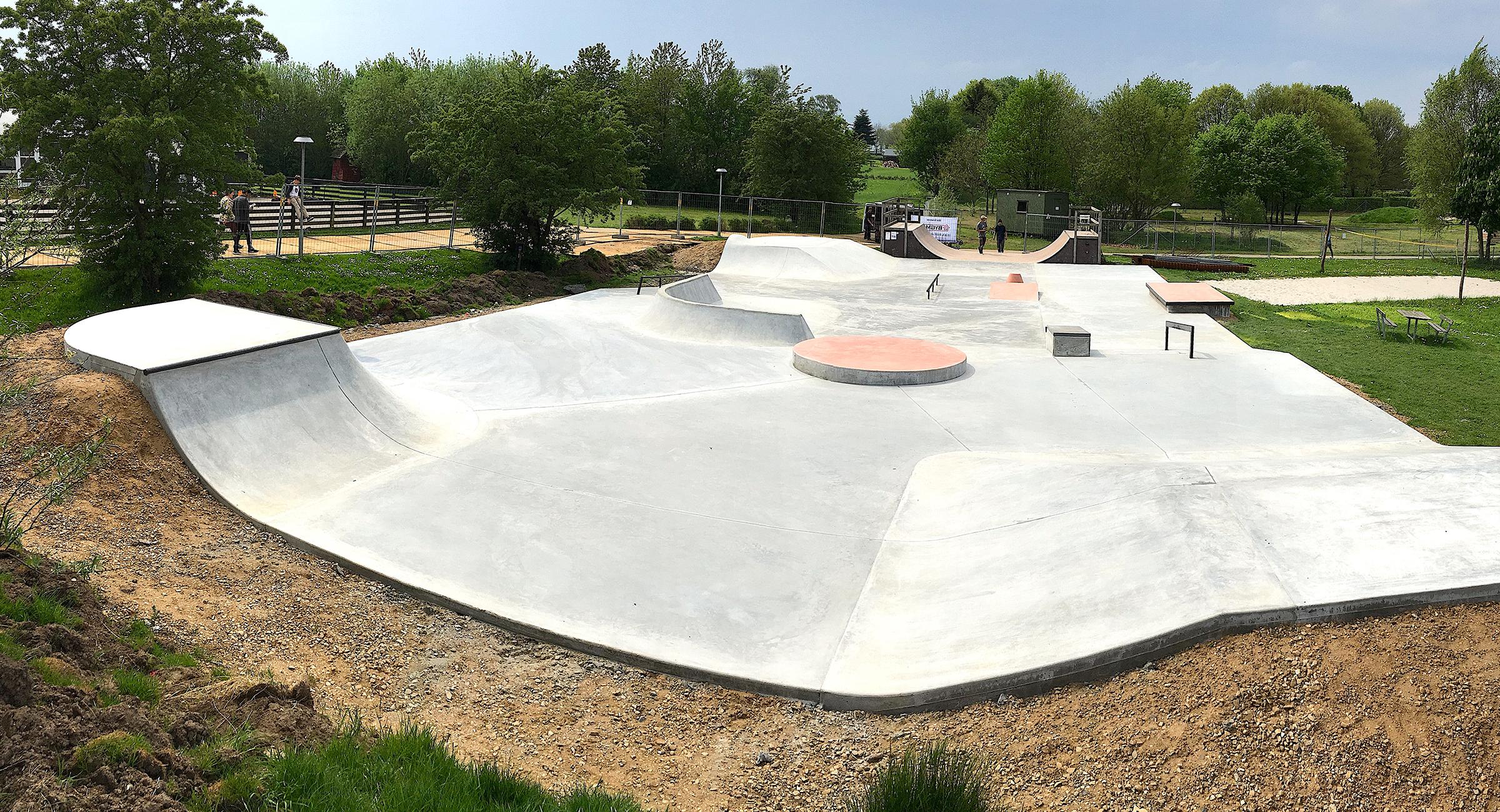 Overbliksbillede over en skatepark i beton med rødmalede overflader