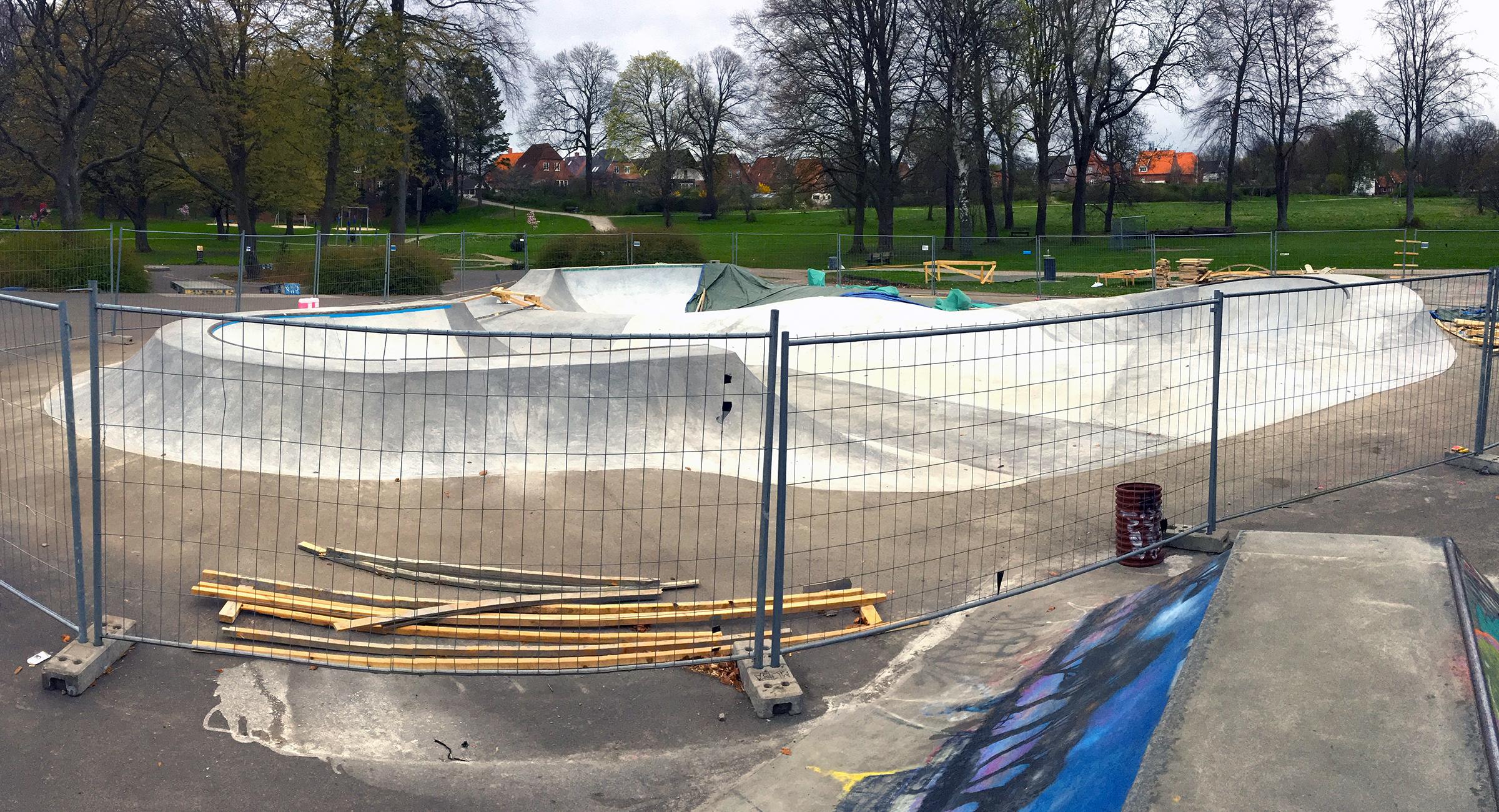 Her ses en indhegnet skatepark under opførsel i en park