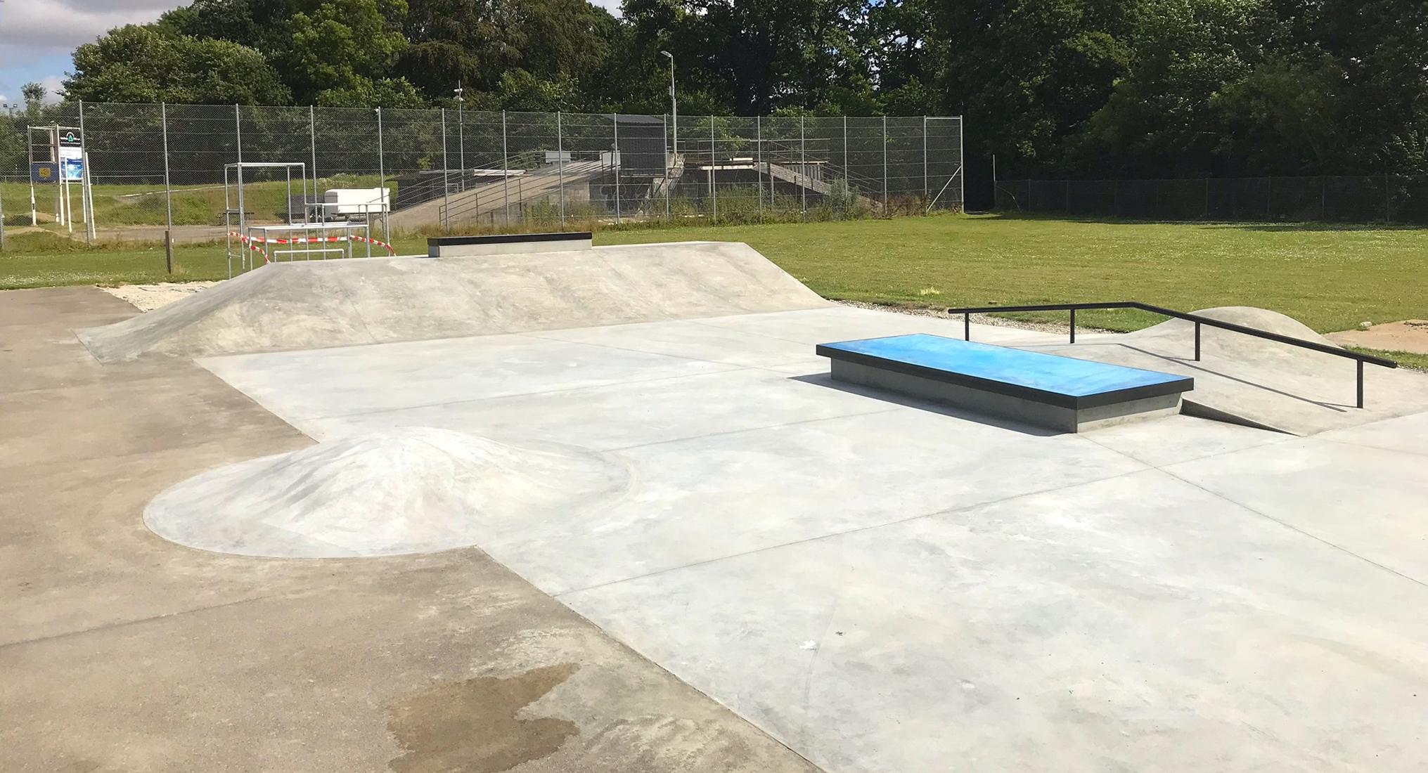 Til venstre ses en lille boble i beton. Til højre ses en curb med blå belægning på toppen