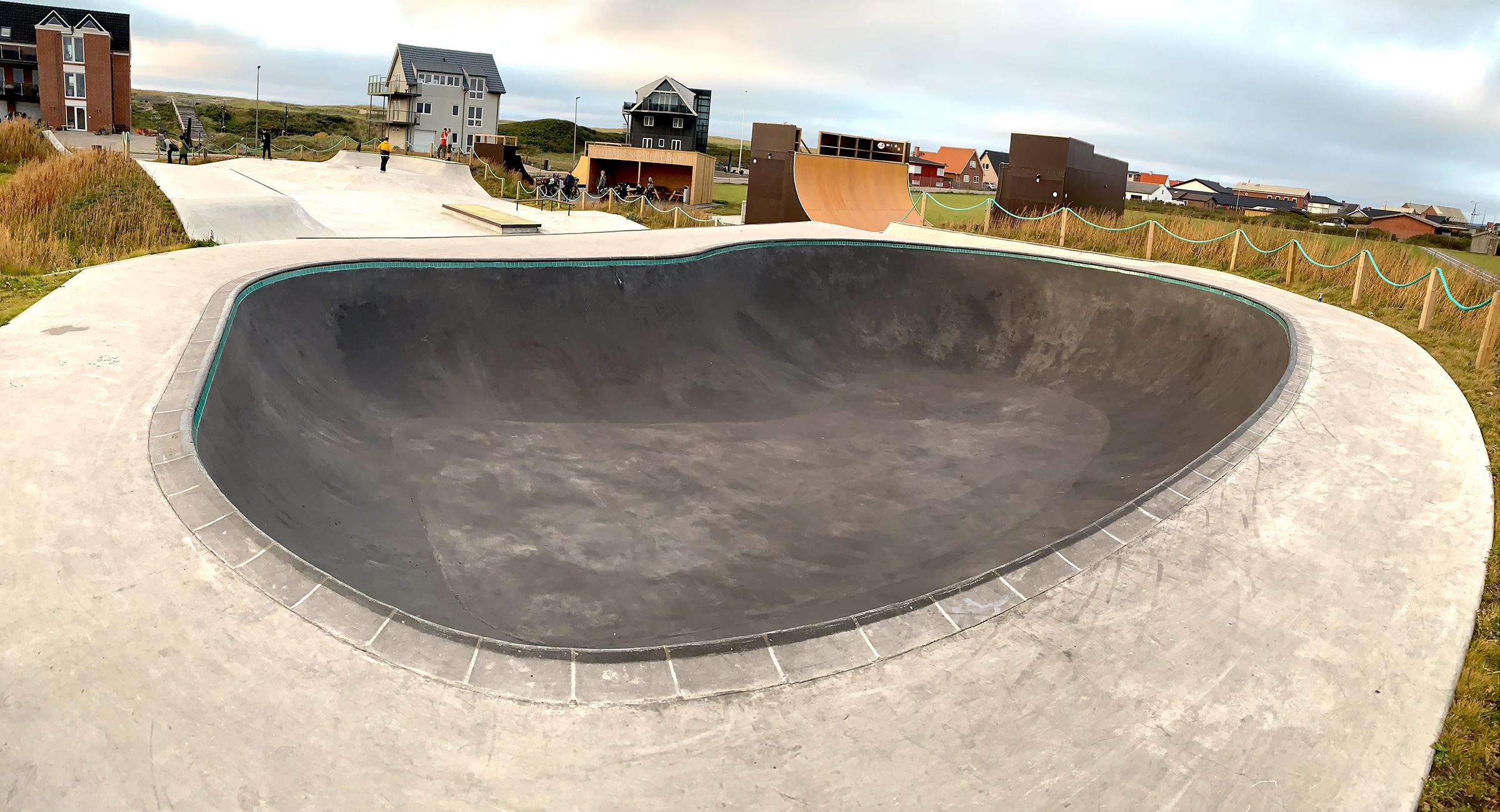 Her ses en stor betonbowl med en skatepark i baggrunden