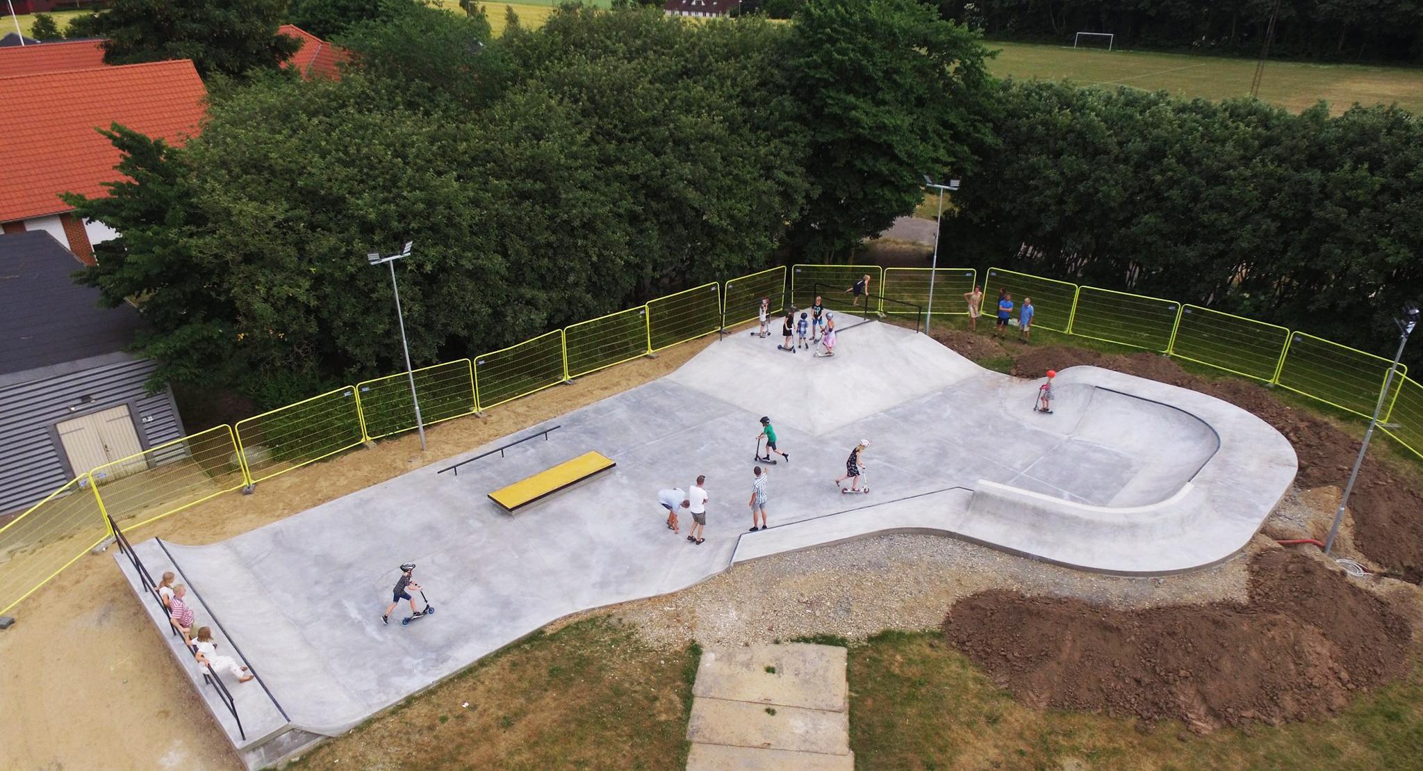Et luftfoto af en beton skatepark fyldt med brugere