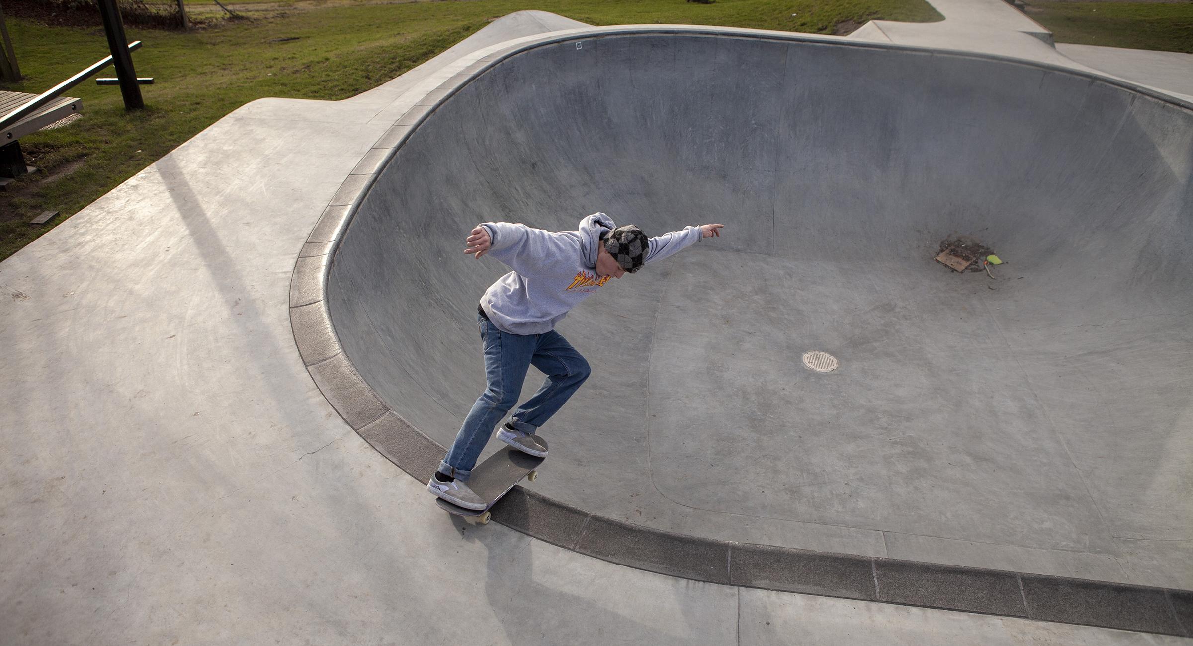 En skater lipslider i hjørnet af en betonbowl