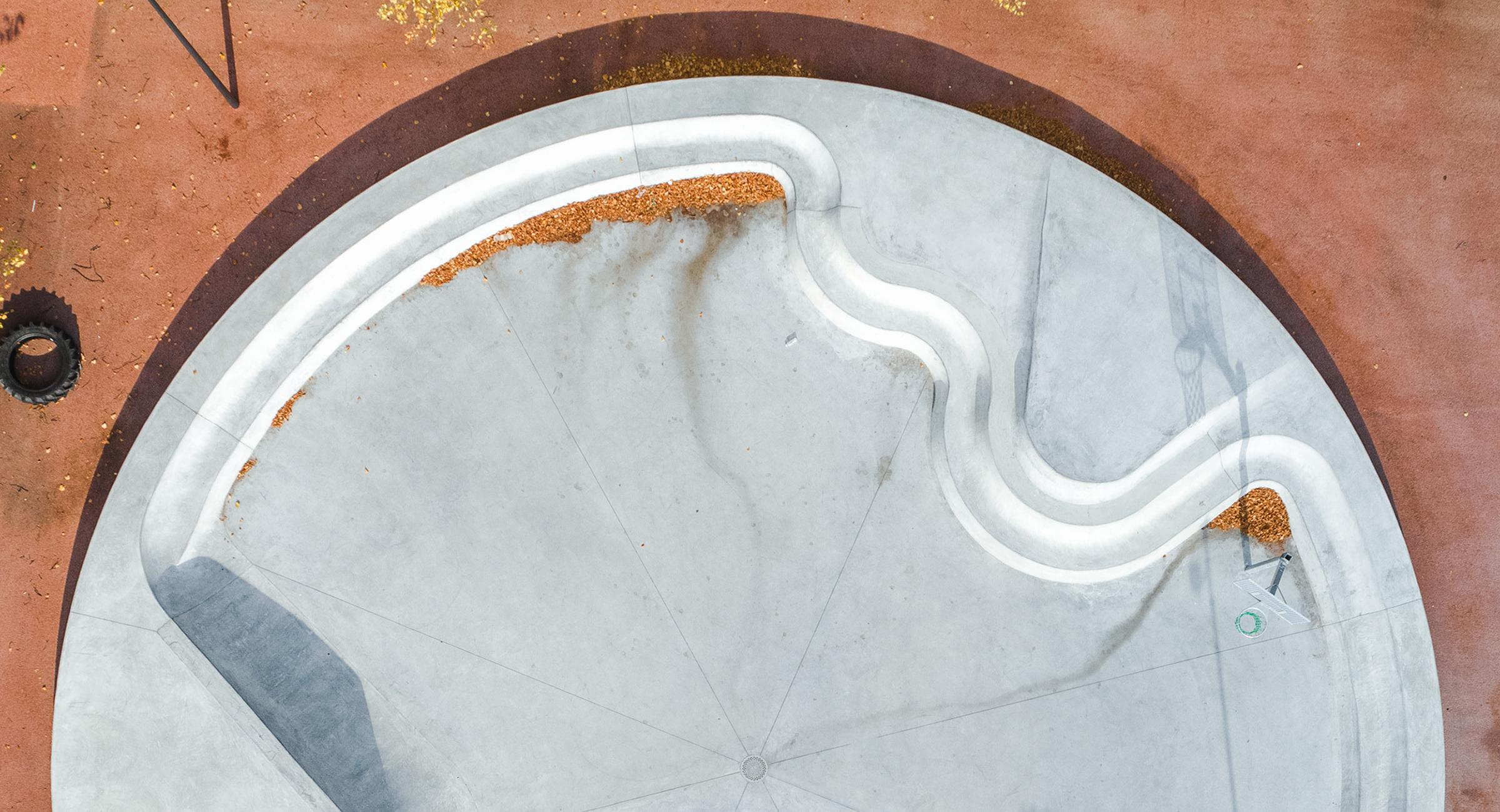 Billedet viser en stor cirkel i beton med kombinerede trapper og siddepladser