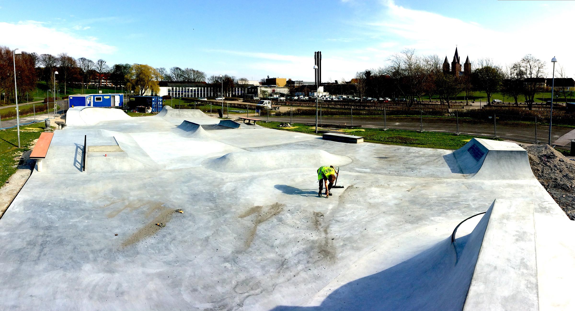 En medarbejder er i gang med at feje i en nybygget beton skatepark