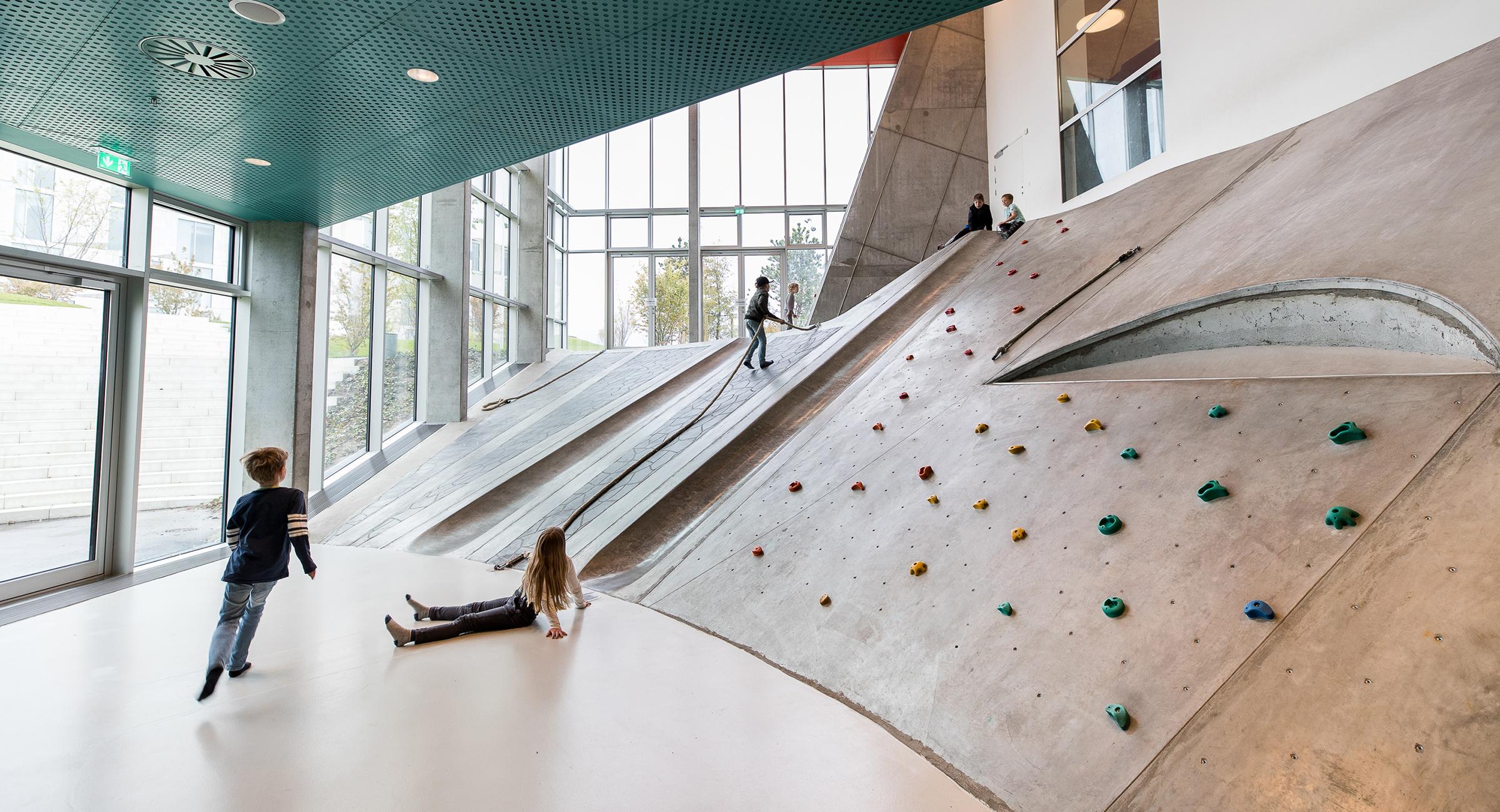 Billedet viser børn i leg på skråt betonunderlag