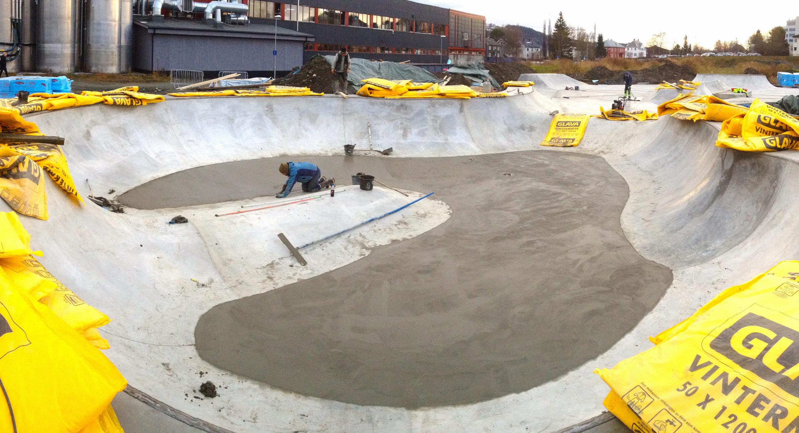 En medarbejder er i gang med at finpudse overgangene mellem et nyt og et tørt lag beton