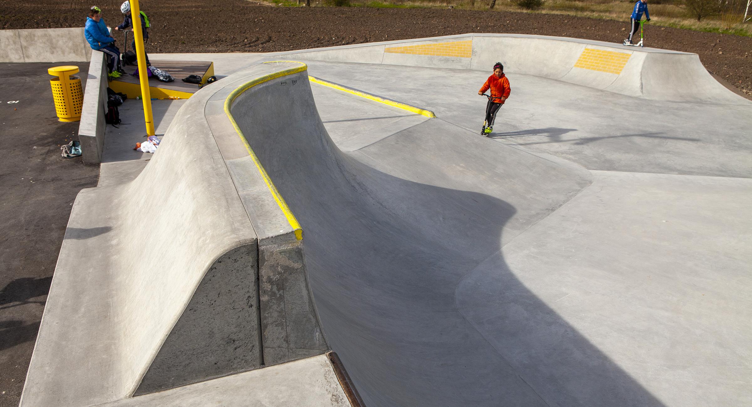 En beton skatepark med forhøjede kanter malet gule