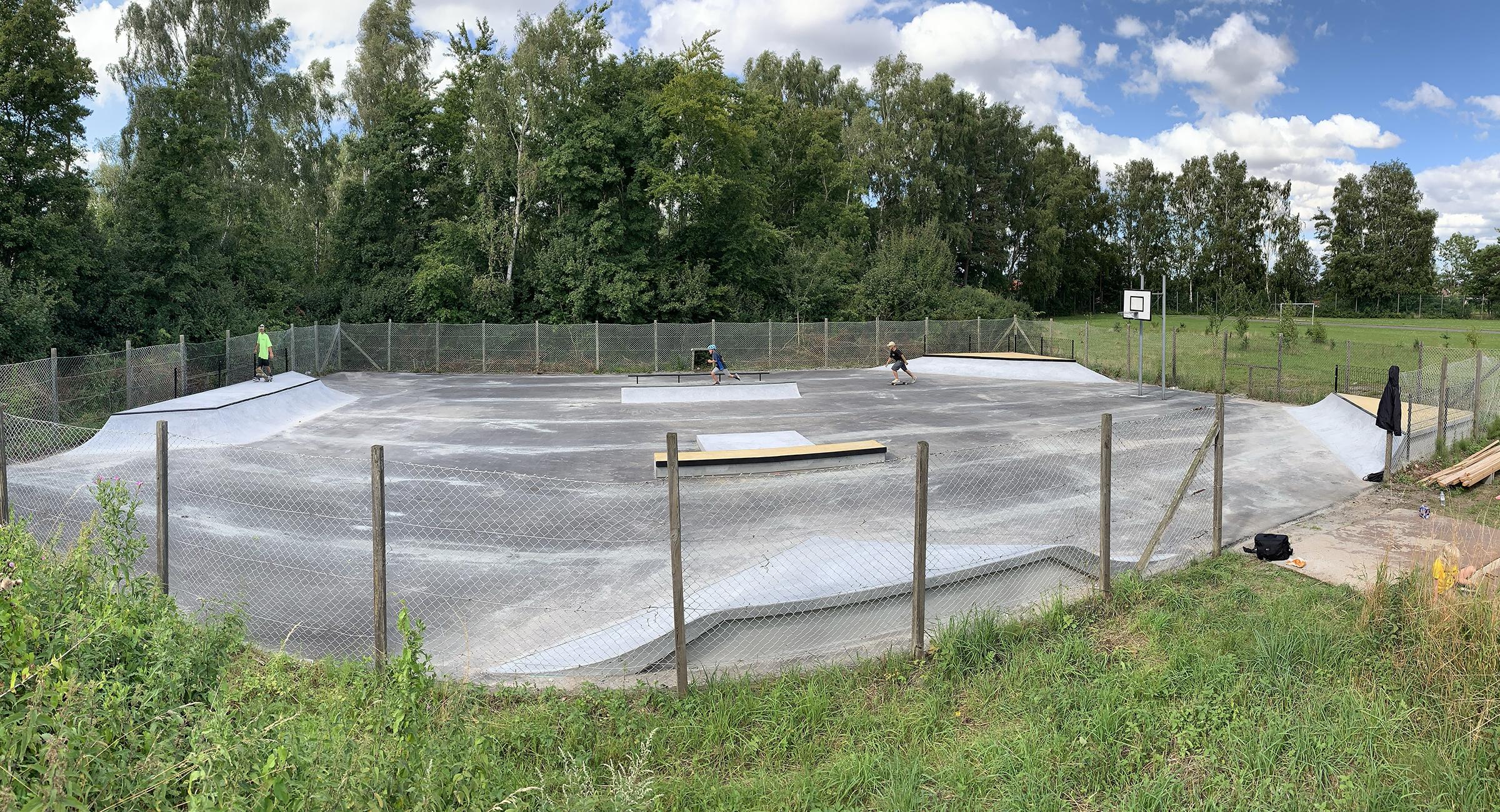 Her ses en indhegnet og asfalteret grund med små skateboardramper i beton